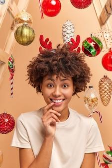 Pionowy obraz szczęśliwej kręconej kobiety uśmiecha się szeroko i ma idealne białe zęby, nosi obręcz jelenia i pozę koszulki