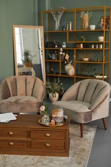 Pionowy obraz tła eleganckiego wnętrza salonu z wygodnymi aksamitnymi fotelami i antycznymi meblami w odcieniach zieleni