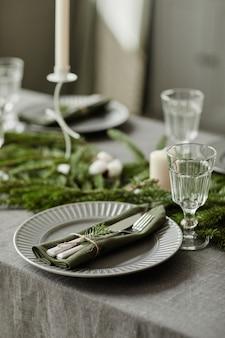 Pionowy obraz tła stołu w jadalni ozdobionego na boże narodzenie gałęziami jodły i ok...