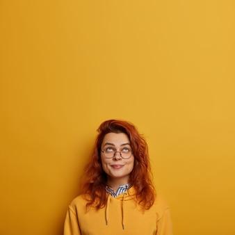 Pionowy obraz uroczej rudej dziewczynki wygląda powyżej, ma zadowolony wyraz twarzy, podnosi głowę, cieszy się słonecznym dniem, nosi duże okulary i bluzę