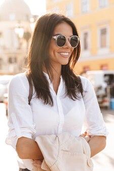 Pionowy obraz uśmiechnięta brunetka kobieta w koszuli i okularach przeciwsłonecznych