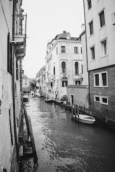 Pionowy obraz w skali szarości przedstawiający kanał z łodziami i starożytnymi budynkami w wenecji we włoszech