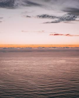 Pionowy obraz z pięknym widokiem na ocean z falami i pomarańczowym horyzontem