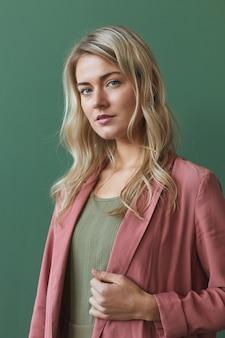 Pionowy pas portret eleganckiej kobiety blondynka ubrana w zakurzoną różową kurtkę i pozując na zielonym tle w studio