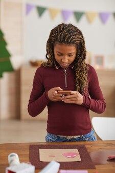 Pionowy pas portret nastoletniej afroamerykanki robiącej zdjęcie ręcznie robionego zdjęcia do opublikowania w mediach społecznościowych