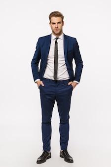 Pionowy pełnej długości atrakcyjny blond pewny siebie i odnoszący sukcesy biznesmen w klasycznym garniturze, krawat, trzymając ręce w kieszeniach, pewny siebie aparat fotograficzny, ściśle określony wyraz, białe tło