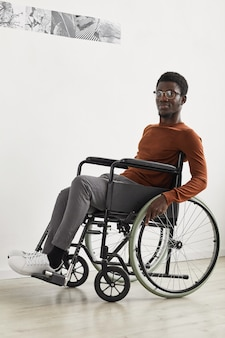 Pionowy pełny portret młodego afroamerykanina na wózku inwalidzkim i podczas zwiedzania wystawy w galerii sztuki współczesnej
