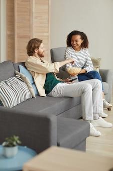 Pionowy pełny portret szczęśliwej pary rasy mieszanej, cieszącej się czasem w domu, oglądając telewizję, relaksując się na wygodnej kanapie i jedząc popcorn