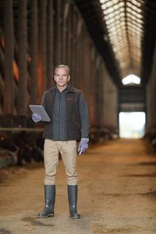 Pionowy pełny portret współczesnego dojrzałego mężczyzny trzymającego cyfrowy tablet podczas inspekcji zwierząt gospodarskich w gospodarstwie mlecznym, miejsce na kopię