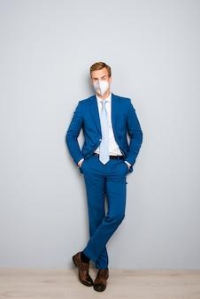 Pionowy pełny rozmiar ciała widok portret atrakcyjny zdrowy elegancki facet ubrany n95 maska bezpieczeństwa wielokrotnego użytku ncov mers infekcja pandemia koncepcja na białym tle na szarym tle koloru