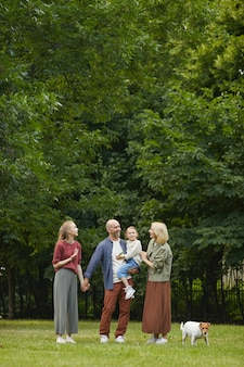 Pionowy portret beztroskiej rodziny z dwójką dzieci i psem stojącym na zielonej trawie na świeżym powietrzu podczas wspólnego spaceru w parku