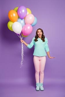 Pionowy portret całego ciała pięknej damy przynosi wiele kolorowych balonów przyjaciołom impreza nosić rozmyty miętowy sweter różowe pastelowe spodnie buty.
