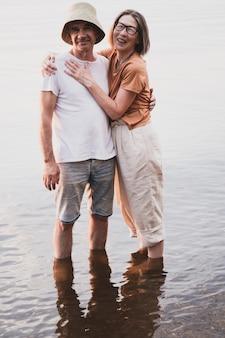 Pionowy portret całego ciała zakochanej pary seniorów stojącej w wodzie na wakacjach