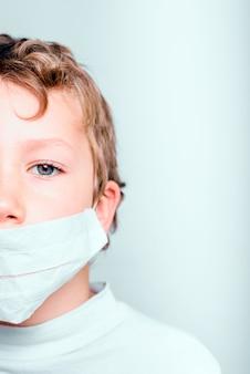 Pionowy portret chłopca na białym tle na ścianie, chory z maską przeciw grypie i koronawirusem.