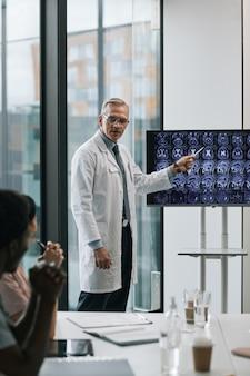 Pionowy portret dojrzałego lekarza przedstawiającego prezentację na konferencji medycznej i wskazującego na zdjęcia rentgenowskie