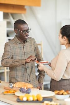Pionowy portret dorosłego mężczyzny i kobiety afroamerykanów rozmawiających i dzielących się jedzeniem podczas kolacji w pomieszczeniu z przyjaciółmi