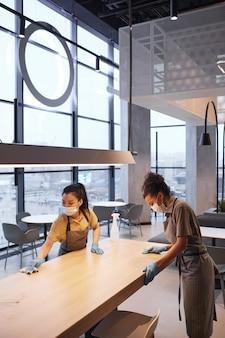 Pionowy portret dwóch pracownic noszących maski podczas czyszczenia stołów w nowoczesnym wnętrzu restauracji, koncepcja bezpieczeństwa covid, kopia przestrzeń