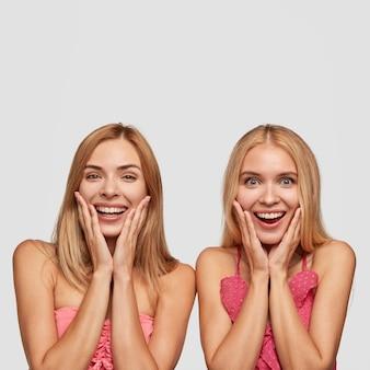 Pionowy portret dwóch radosnych dziewczyn z szerokimi uśmiechami, zdumionych, gdy widzą coś niesamowitego i miłego, stojących obok siebie