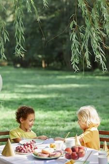 Pionowy portret dwójki małych dzieci przy stole piknikowym na zewnątrz, cieszących się przyjęciem urodzinowym w lecie...
