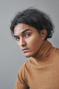 Pionowy portret egzotycznego młodzieńca pochodzenia indiańskiego, pozując na szarym tle, unikalna koncepcja piękna