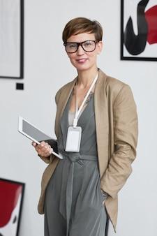 Pionowy portret eleganckiej, kreatywnej kobiety uśmiechającej się do kamery i trzymającej cyfrowy tablet podczas planowania wystawy w galerii sztuki,