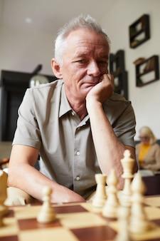 Pionowy portret kaukaskiego starszego mężczyzny grającego w szachy i cieszącego się zajęciami w domu opieki