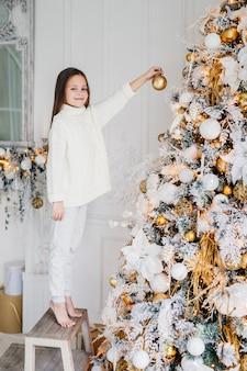 Pionowy portret kobiecego dziecka stoi w pobliżu drzewa sylwestrowego, trzyma ozdobioną bombkę noworoczną, ozdabia jodłę, ma szczęśliwy wyraz twarzy, antycypuje cud. rodzina, boże narodzenie, wakacje, dzieci