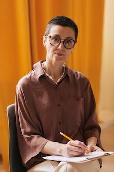 Pionowy portret krótkowłosej kobiety psycholog patrzącej na kamerę i trzymającej schowek podczas konsultacji z klientem