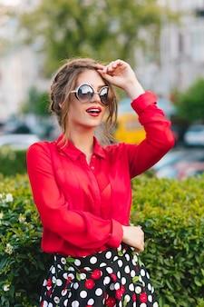 Pionowy portret ładnej dziewczyny w okularach przeciwsłonecznych, pozowanie do kamery w parku. nosi czerwoną bluzkę, czarną spódnicę i ładną fryzurę. ona patrzy daleko.