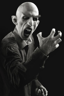 Pionowy portret mężczyzny oznaczonego jako wampir na czarnym tle.