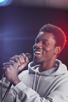 Pionowy portret młodego mężczyzny afroamerykańskiego namiętnie śpiewającego do mikrofonu, stojąc na scenie w światłach
