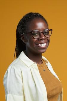 Pionowy portret młodej afroamerykanki w okularach i uśmiechniętej radośnie do kamery podczas...