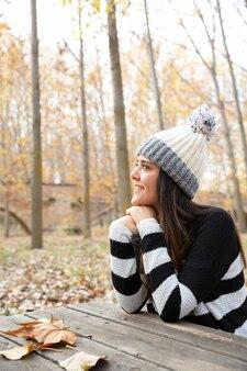 Pionowy portret młodej dziewczyny w zimowe ubrania siedzi na ławce, ciesząc się jesienny dzień. miejsce na tekst.