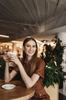 Pionowy portret młodej kobiety eleganckiej, ciesząc się filiżanką kawy, siedząc w kawiarni.