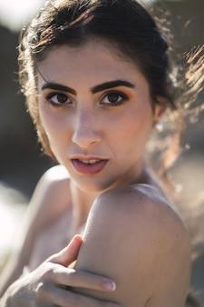 Pionowy portret młodej kobiety rasy kaukaskiej brunetka o ciemnobrązowych oczach