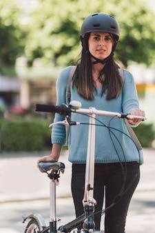 Pionowy portret młodej kobiety w kasku stojącej obok roweru na ulicy