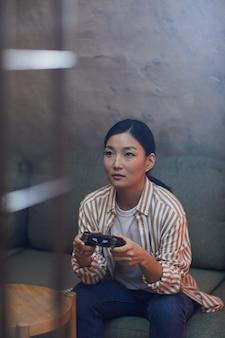 Pionowy portret młodej kobiety z azji grającej w gry wideo za pośrednictwem konsoli do gier