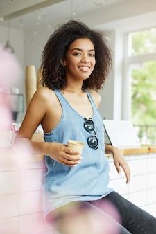 Pionowy portret młodej, ładnej, wesołej, ciemnoskórej africal studentki z falującymi włosami w niebieskiej koszuli, siedzącej w kawiarni, pijącej latte, uśmiechającej się, patrzącej w kamerę z radością i relacją