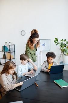 Pionowy portret młodej nauczycielki pomagającej dzieciom korzystać z laptopów podczas lekcji it w szkole