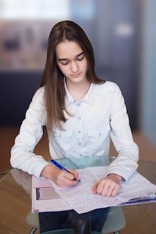 Pionowy portret młodej poważnej pięknej dziewczyny z długimi blond włosami z jej pracy domowej na niewyraźne tło. nastoletnia uczennica trzyma długopis i pisze w notesie. przedni widok.