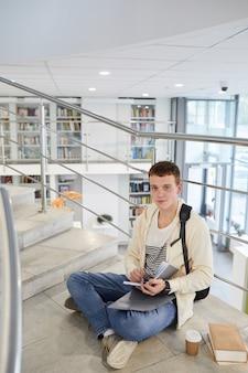 Pionowy portret pełnej długości młodego mężczyzny siedzącego na schodach w bibliotece uczelni i podczas pracy domowej