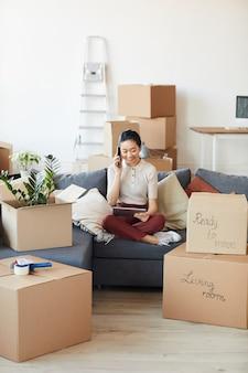 Pionowy portret pełnej długości nowoczesnej azjatki rozmawiającej przez telefon podczas rozpakowywania pudeł w nowym domu lub mieszkaniu