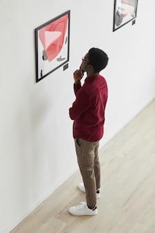 Pionowy portret pod dużym kątem młodego mężczyzny afroamerykańskiego patrzącego na obrazy i myślącego w galerii sztuki lub na wystawie muzealnej,
