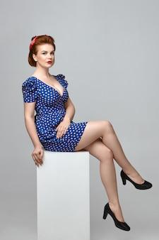 Pionowy portret poważnej, atrakcyjnej młodej dziewczyny pin up z dużym biustem i jasnym makijażem pozowanie na białym tle, ubrana w eleganckie czarne buty, niebieską sukienkę i czerwoną opaskę, mająca pewny siebie wygląd