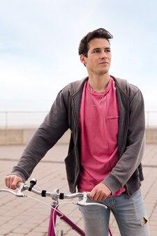 Pionowy portret przystojnego młodego mężczyzny chodzącego z zabytkowym rowerem