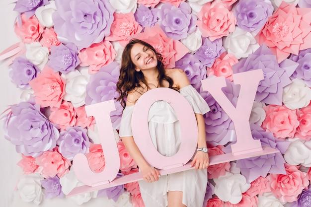 Pionowy portret śliczna brunetka dziewczyna. stoi i trzyma szeroko uśmiechnięte drewniane słowo joy. ma różowe tło pokryte kwiatami
