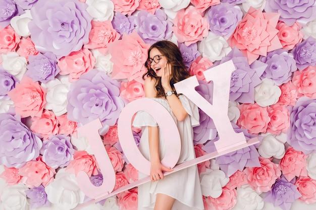 Pionowy portret śliczna brunetka dziewczyna. stoi i trzyma szeroko uśmiechnięte drewniane słowo joy. tło w różowe kwiaty