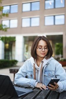 Pionowy portret ślicznej uśmiechniętej młodej kobiety rasy kaukaskiej, student siedzi na ławce z laptopem na świeżym powietrzu, używa telefonu komórkowego, czyta tekst z uśmiechem, łączy się z internetem wifi, czeka na przyjaciela.