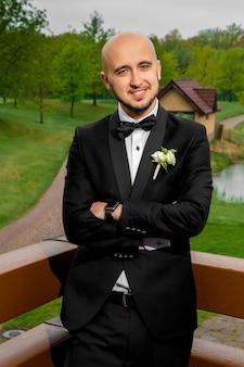 Pionowy portret wesoły elegancki mężczyzna w garniturze pozowanie na zewnątrz