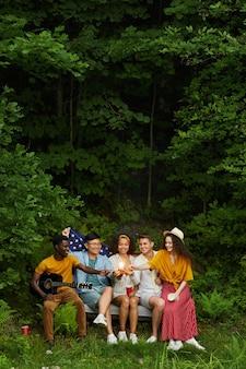 Pionowy portret wieloetnicznej grupy ludzi pije piwo i gra na gitarze siedząc na ławce w lesie i ciesząc się wakacjami